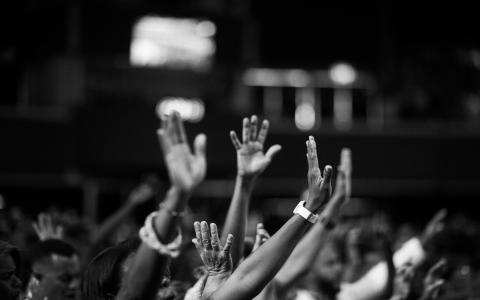 black and white photo of crowd with hands raised in worship